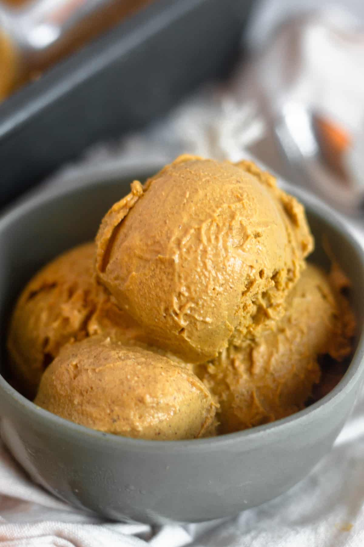 Small green bowl filled with dairy free paleo pumpkin ice cream sitting on a tan linen