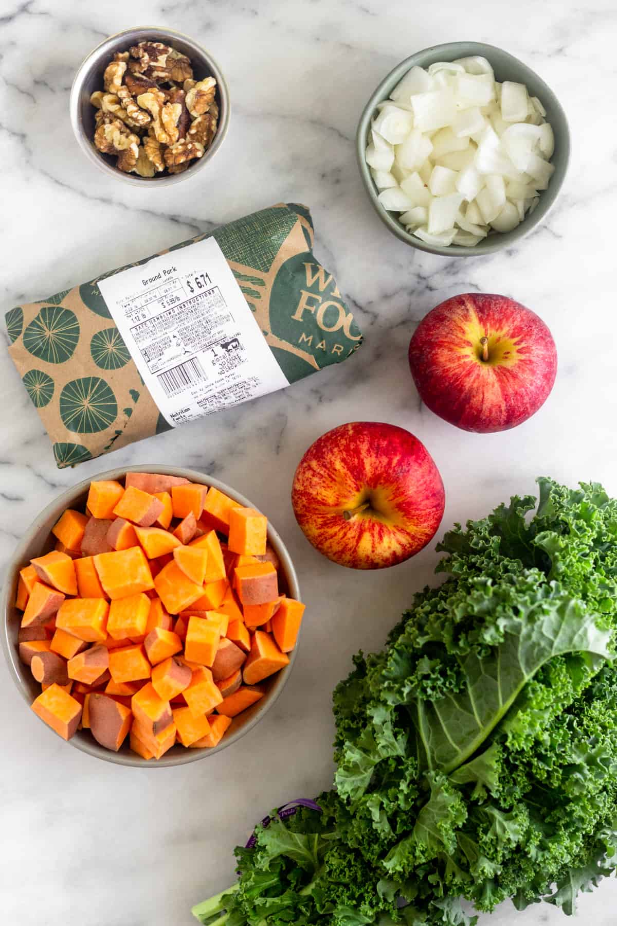 White counter with a small bowl of walnuts, bowl of diced onions, 2 apples, bunch of kale, bowl of diced sweet potatoes, and a package of ground pork.