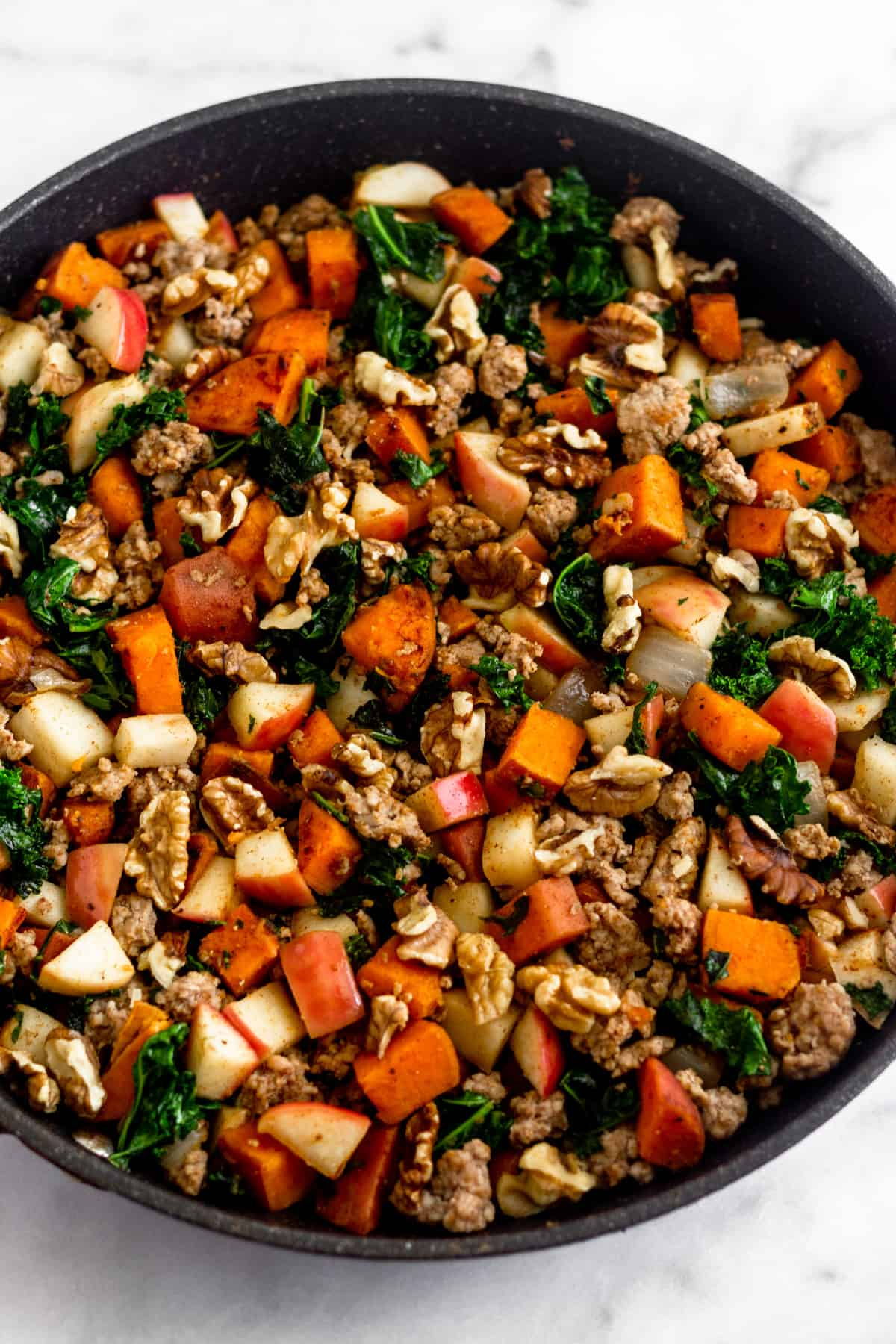 Large saute skillet filled with sweet potatoes, sausage, apples, kale, onions, and walnuts.