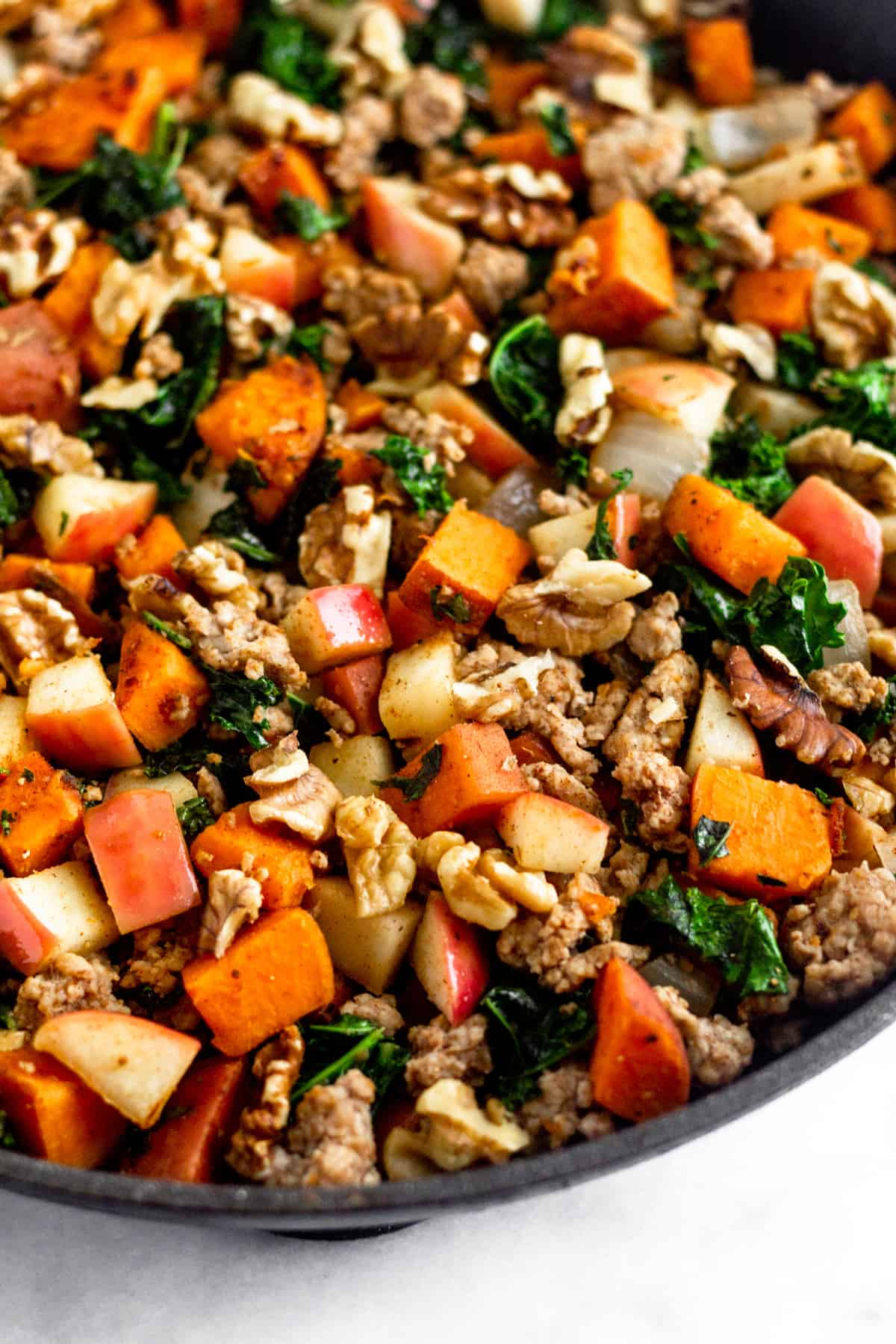 Close up of a large saute pan of of ground pork, sweet potatoes, kale, apples, and walnuts.