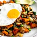 White plate on a tan linen with sweet potato sausage hash topped with a fried egg and sliced avocado.