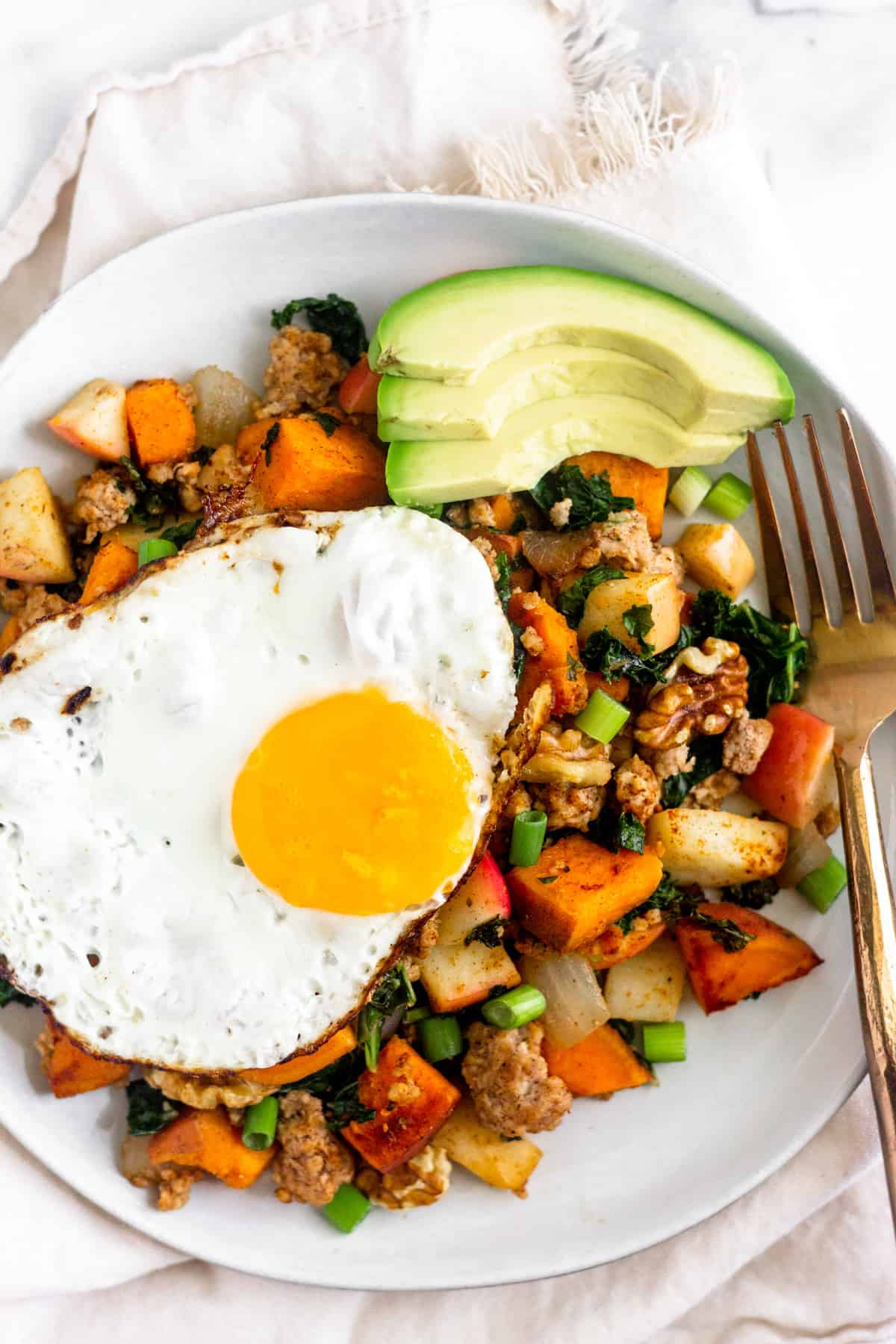 White plate on a tan linen filled with Whole30 Sweet Potato Sausage Hash, a fried egg, sliced avocado, and a bronze fork.