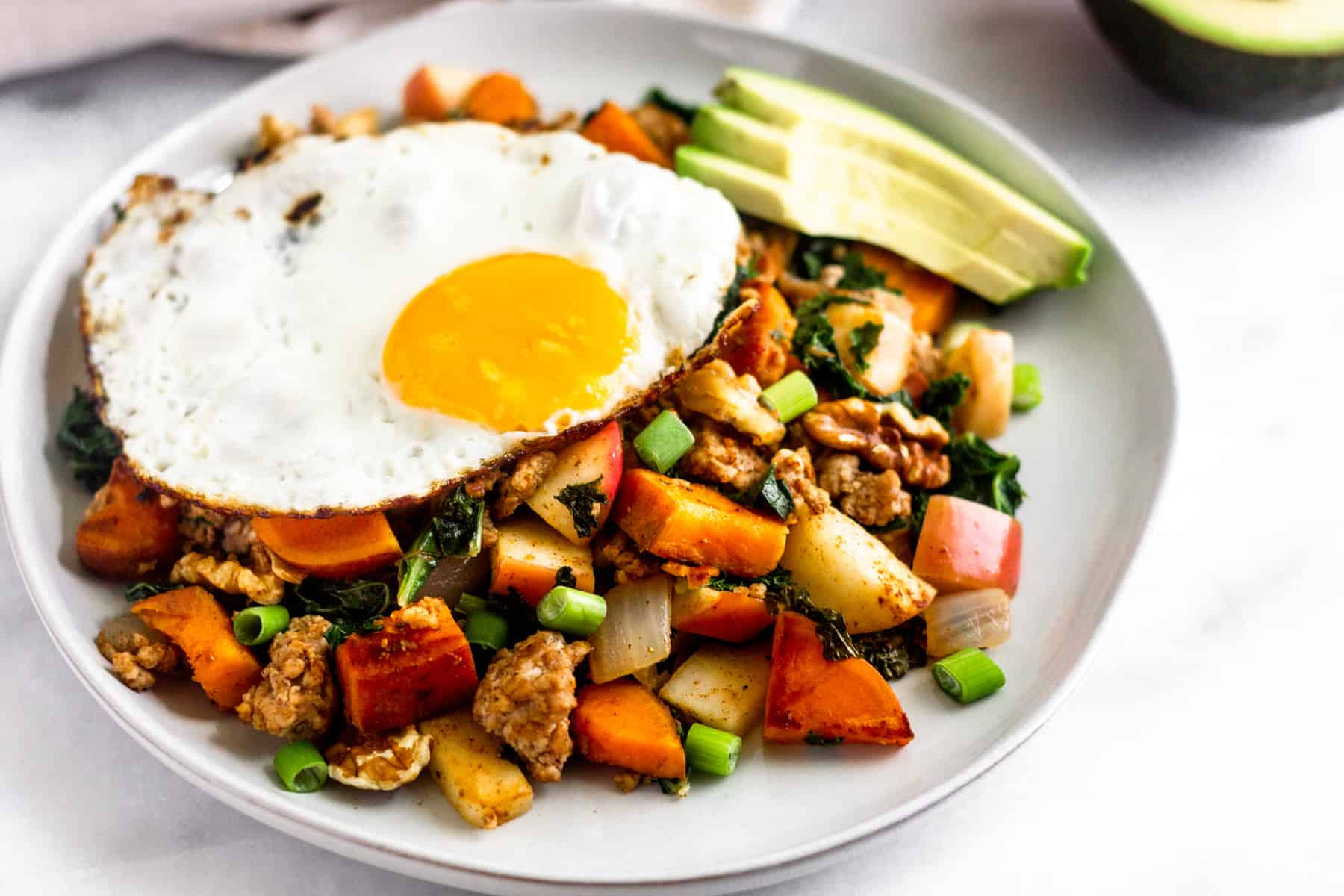White plate with sausage apple hash, a fried egg, and sliced avocado.