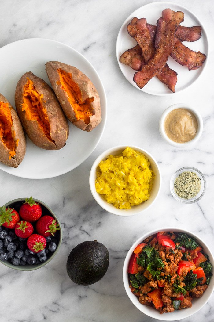 Overhead shot of 3 baked sweet potatoes on a plate, a plate of crispy bacon, bowl of scrambled eggs, bowl of chorizo and veggies, an avocado, and a bowl of berries.