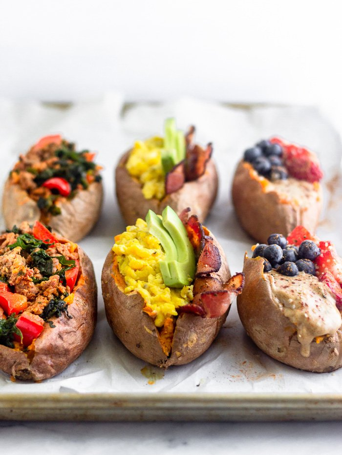 Six different stuffed sweet potatoes on a baking sheet. There are three different varieties.