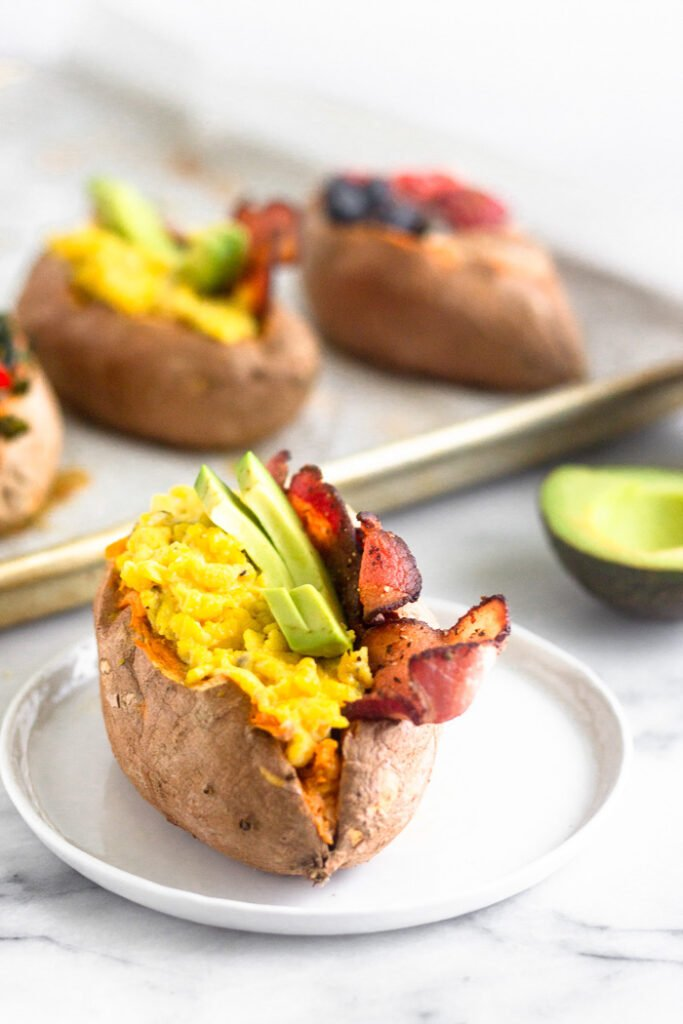 Breakfast stuffed sweet potato filled with scrambled eggs, bacon, and avocado. Behind it are more stuffed sweet potatoes.