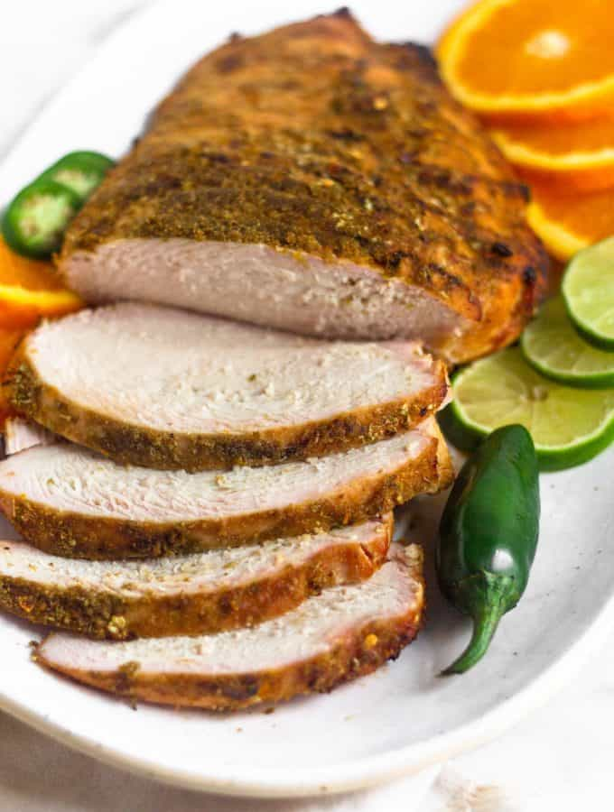 Citrus grilled turkey breast with a few pieces cut laying on a plate next to some sliced limes, oranges, and a jalapeño.