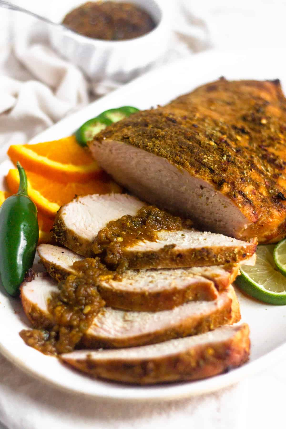 A platter of citrus grilled turkey breast with a spicy citrus sauce overtop the cut pieces