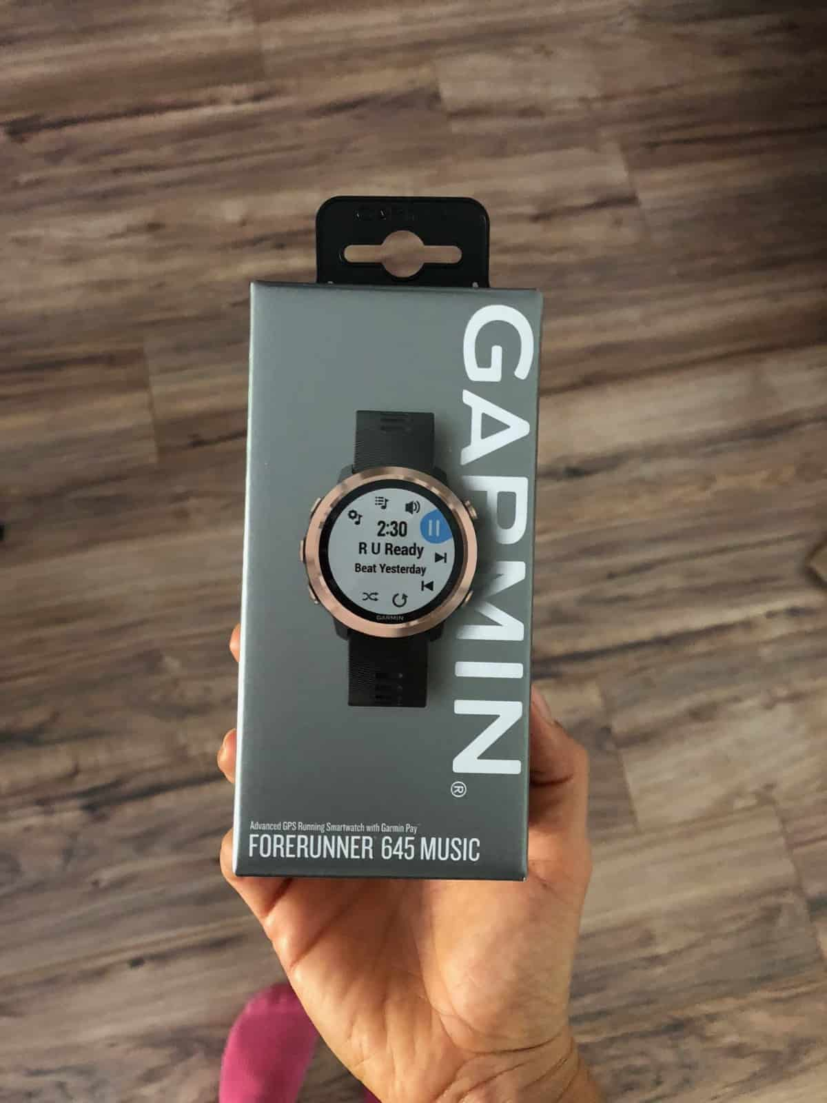 Un-open box of a Garmin Forerunner 645. The watch is black and gold.