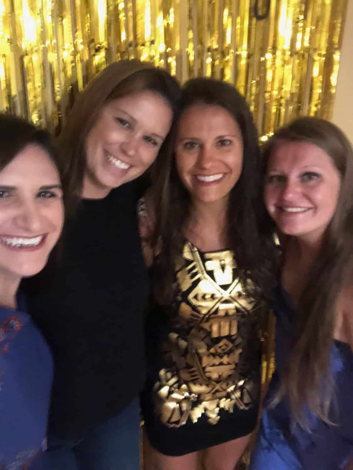 Four dark haired girls in front of a gold streamer, They are dressing up and ready to go out.