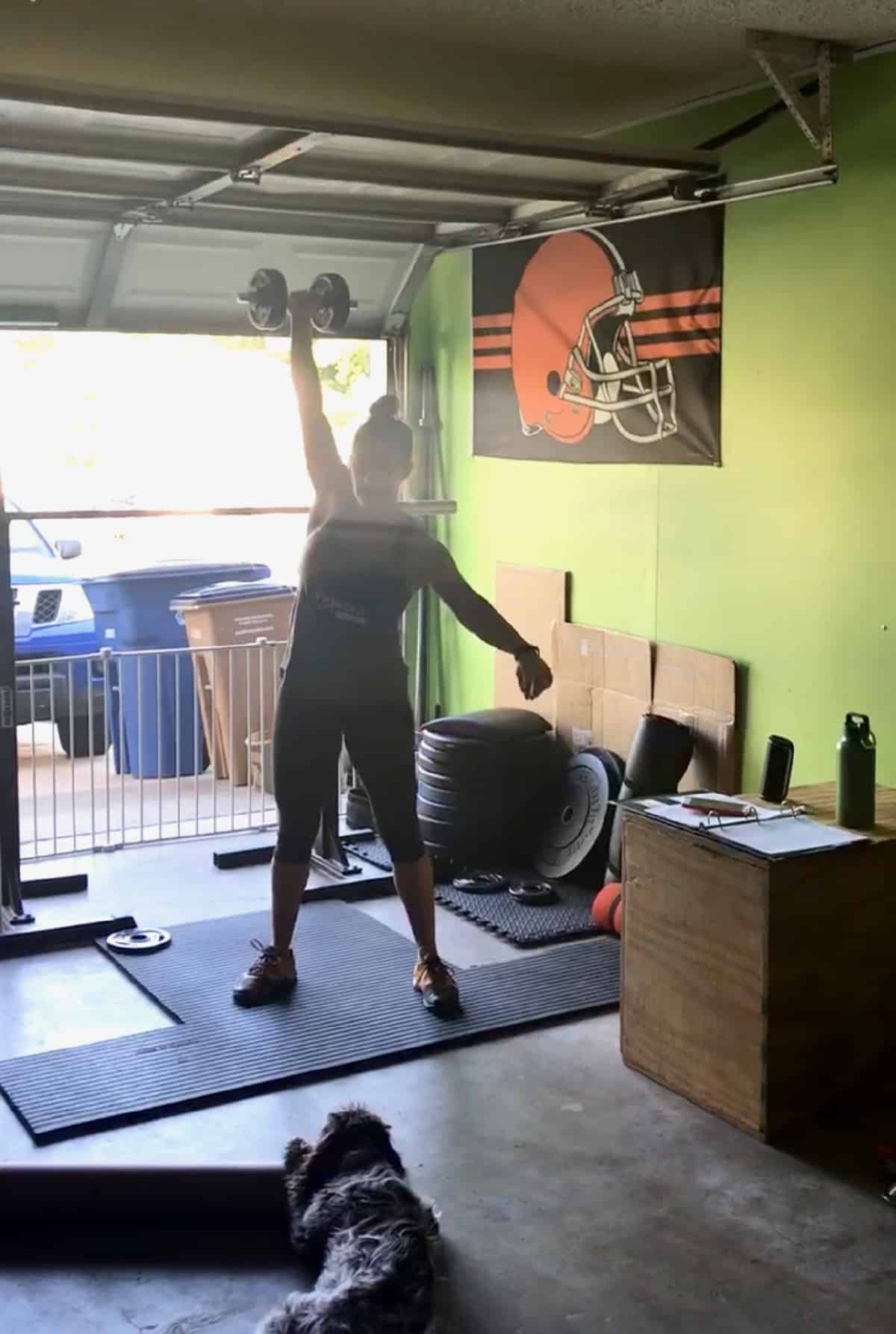 Girl in a garage gym doing a one arm dumbbell snatch