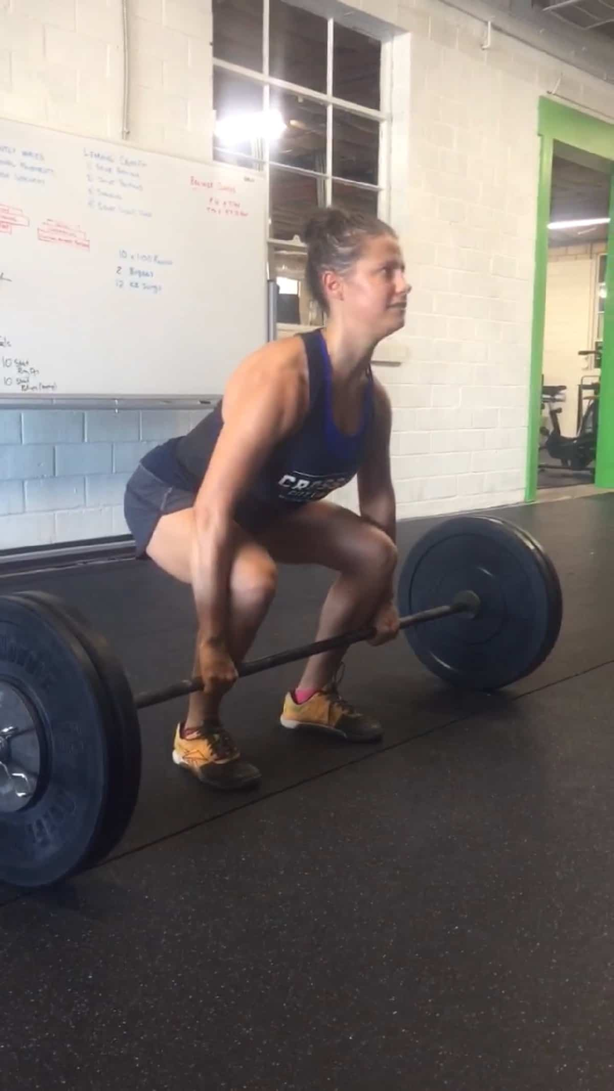 Girl squatting and holding onto a barbell about to do a power clean in a CrossFit gym