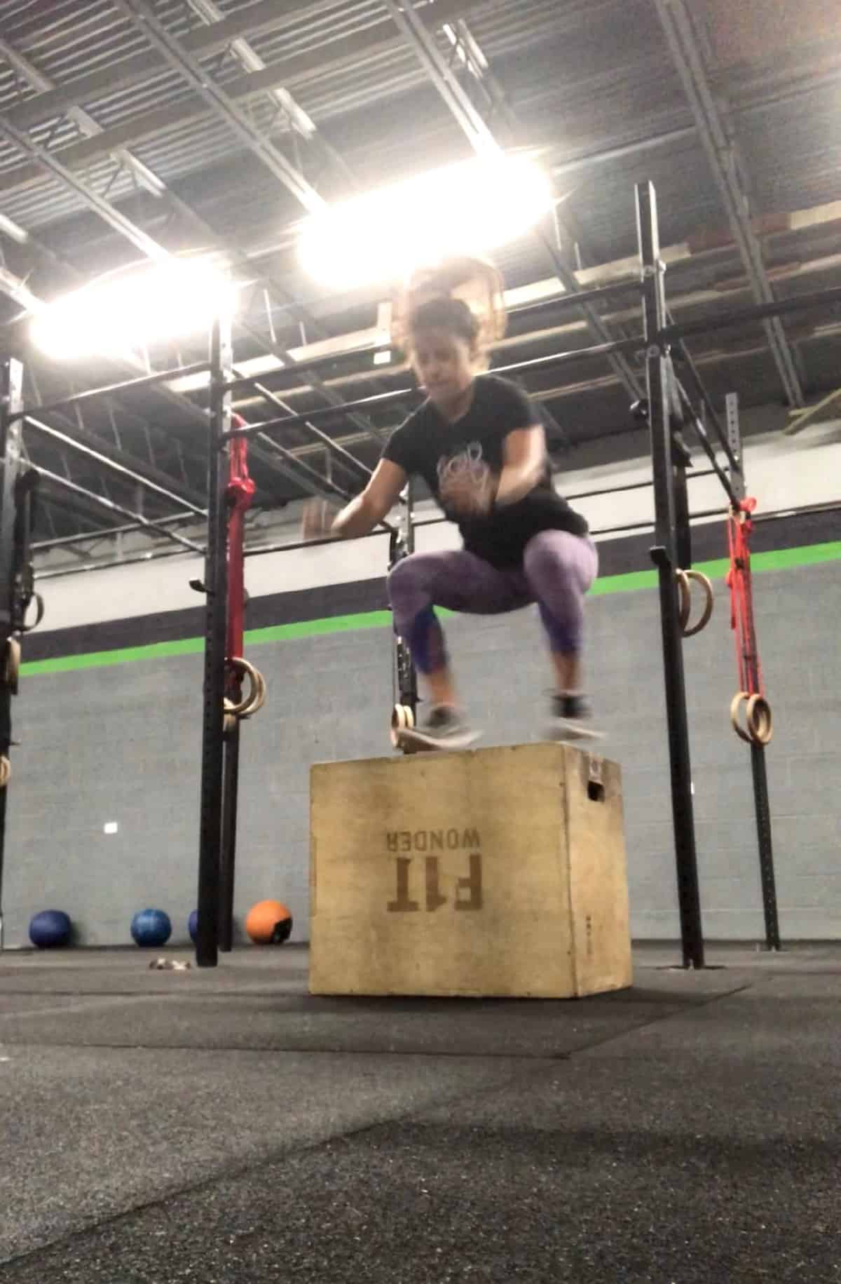 Girl jumping up onto a wooden box doing a box jump