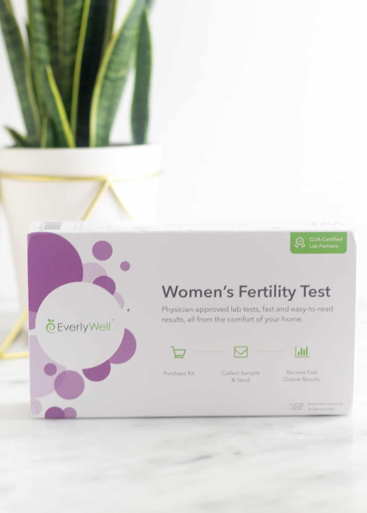 Women's Fertility Testing at Home with EverlyWell box with a plant behind it