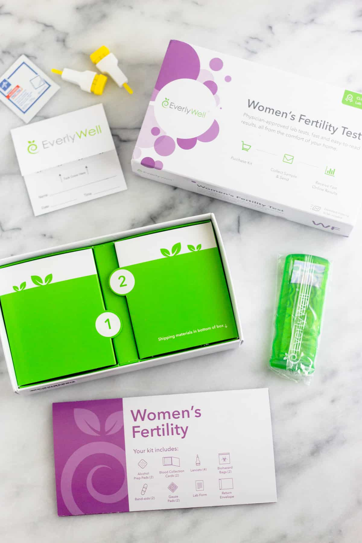 Inside of the package of a Women's Fertility Testing at Home with EverlyWell. Shows the instructions, bandaids, finger prickers, and a cleaning pad.