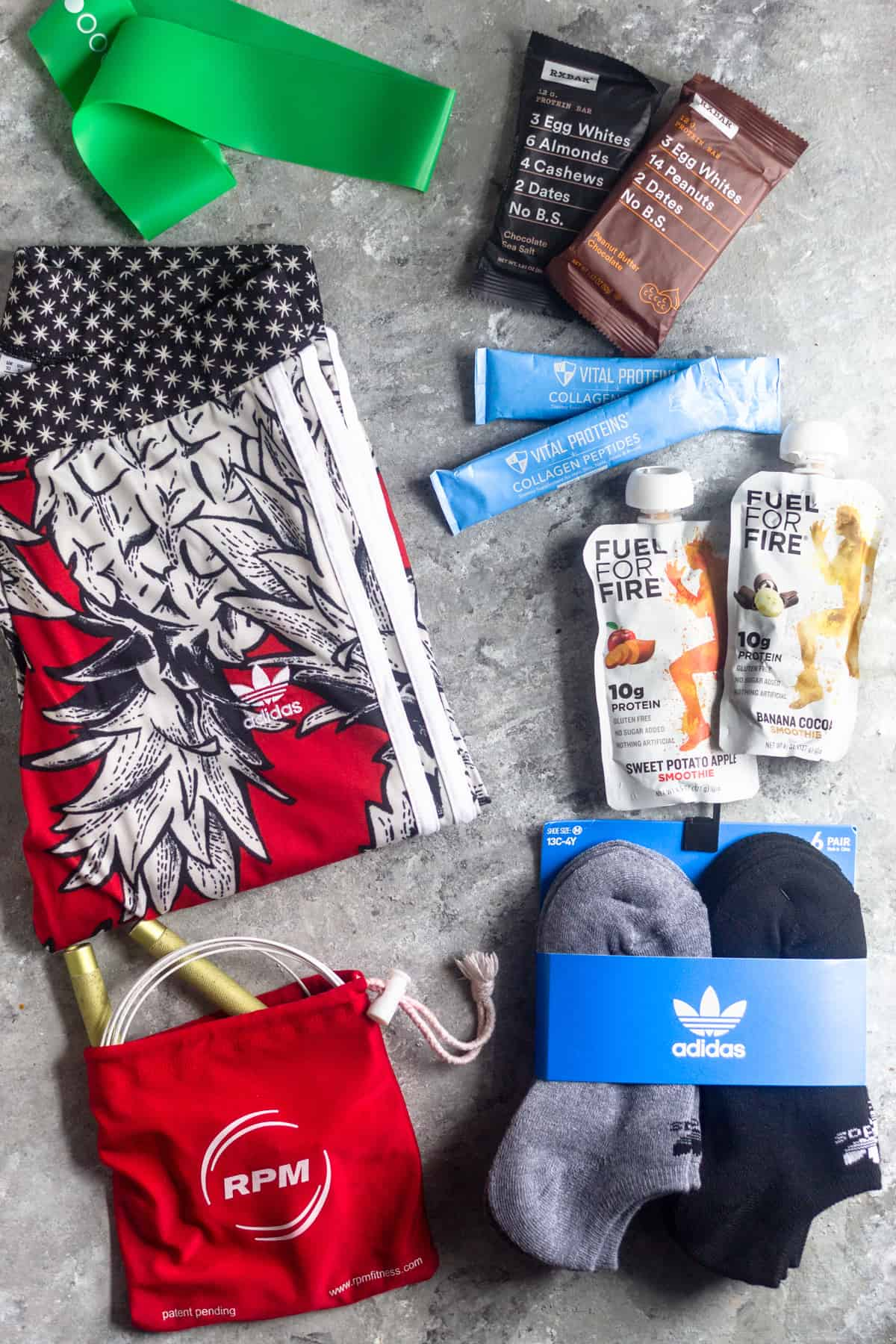 A bunch of items in a holiday gift guide for active women laid out on a grey surface. The items consist of leggings, snacks, socks, a jump rope, and a resistance band.