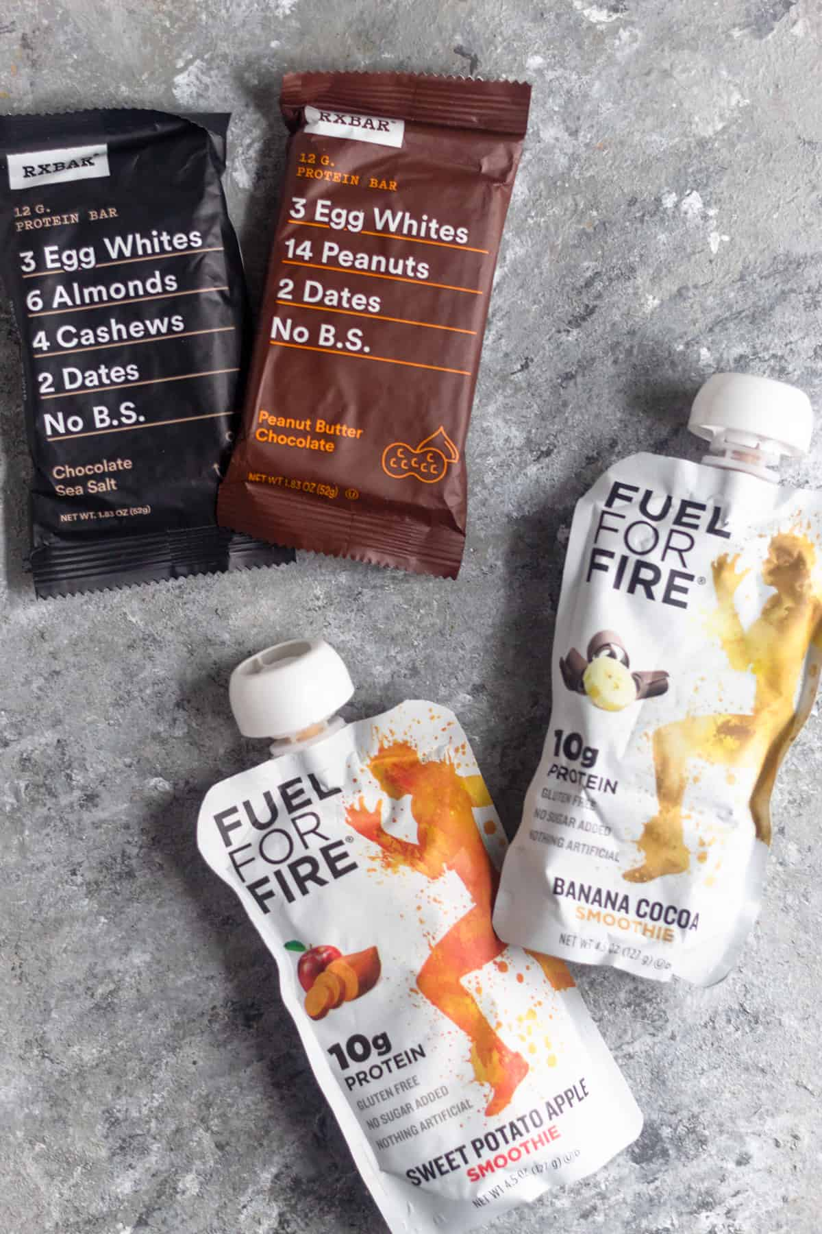 Two RXbars and two Fuel for Fire packets on a grey surface