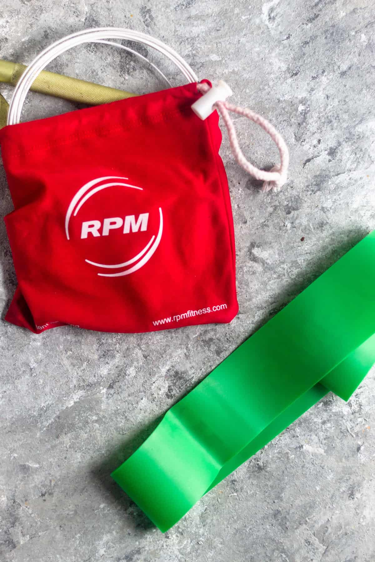 A jump rope in a small red bag and a green resistance band on a grey surface