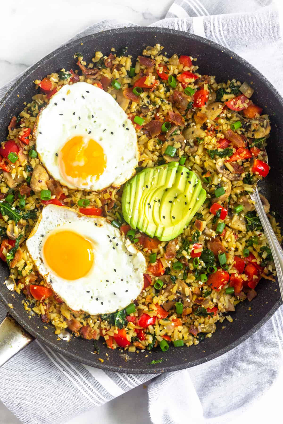 Large saute pan filled with whole30 and paleo breakfast fried rice topped with two fried eggs, sliced avocado, and sesame seeds