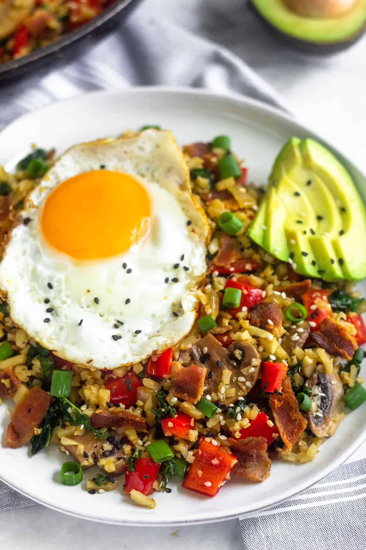 Large white plate filled with whole30 and paleo breakfast fried rice topped with a fried egg, avocado slices, and sesame seeds