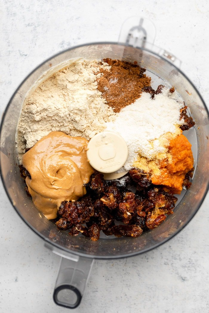 Food processor with pieces of dates that have been processed, cashew butter, protein powder, spices, coconut flour, and pumpkin puree in it.