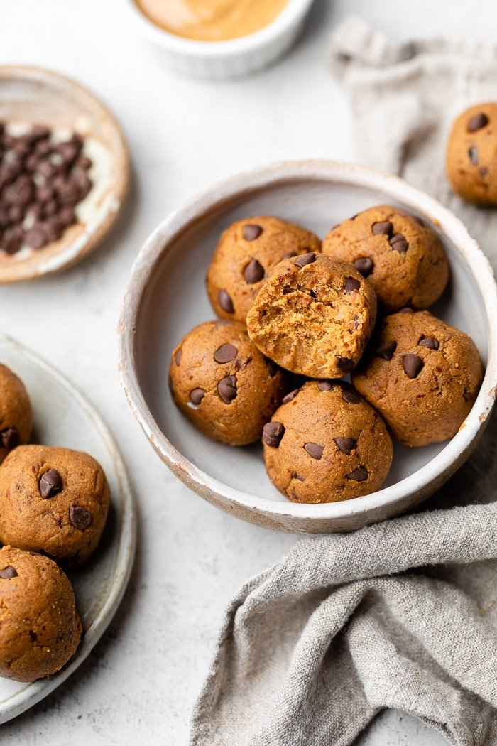 Small bowl of pumpkin protein balls with the top one having a bite taken out of it. Next to it is a plate of more protein balls, small bowls of chocolate chips, bowl of nut butter, and a light tan linen.