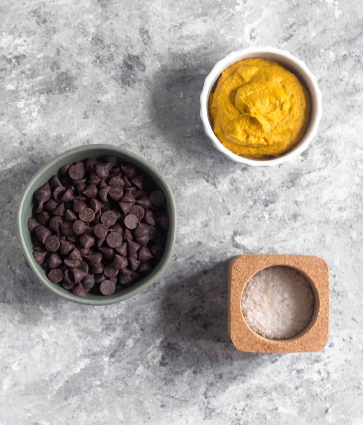 A bowl of chocolate chips, a bowl of pumpkin pie butter, and a container of sea salt on a grey surface