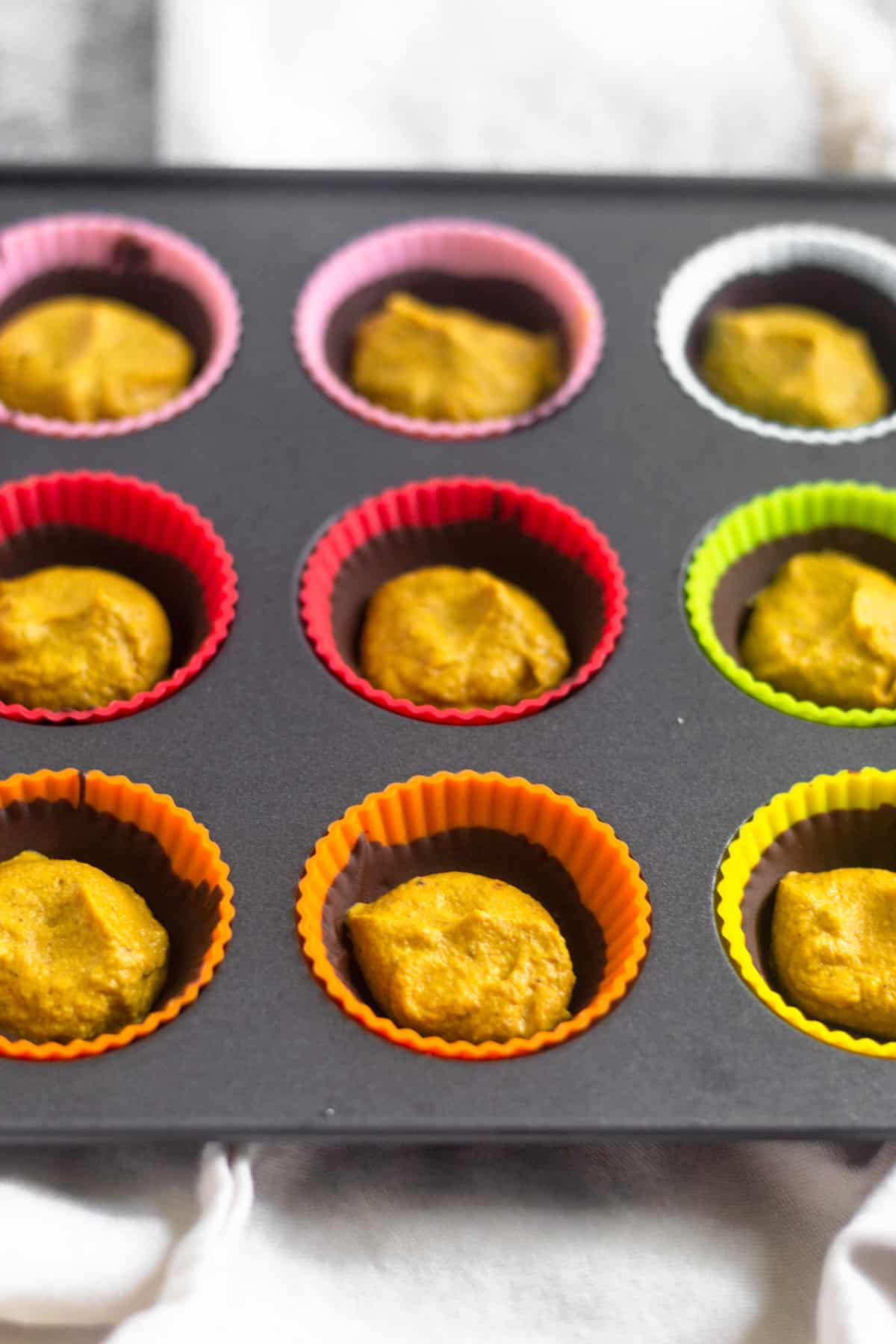 Mini muffin tin tray with half made pumpkin pie chocolate cups in them. There is a shell of chocolate and then a scoop of pumpkin pie butter in them.
