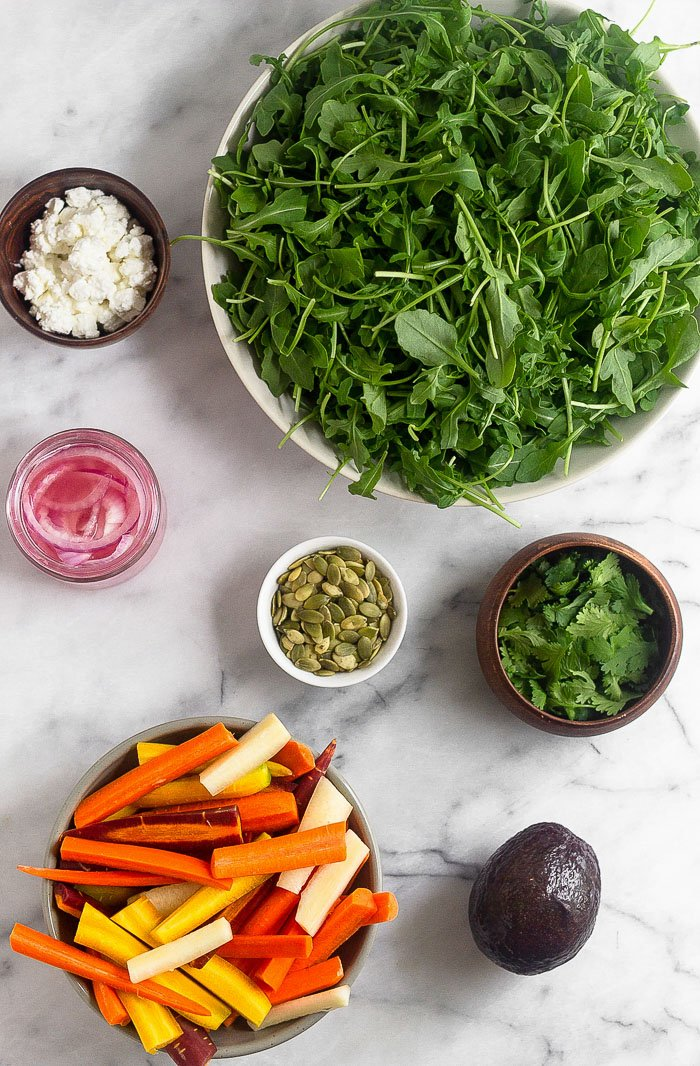 Marble board with a big bowl of arugula, small bowl of cilantro, an avocado, small bowl of cut carrots, small bowl of pumpkin seeds, jar of picked onions, and a bowl of feta cheese