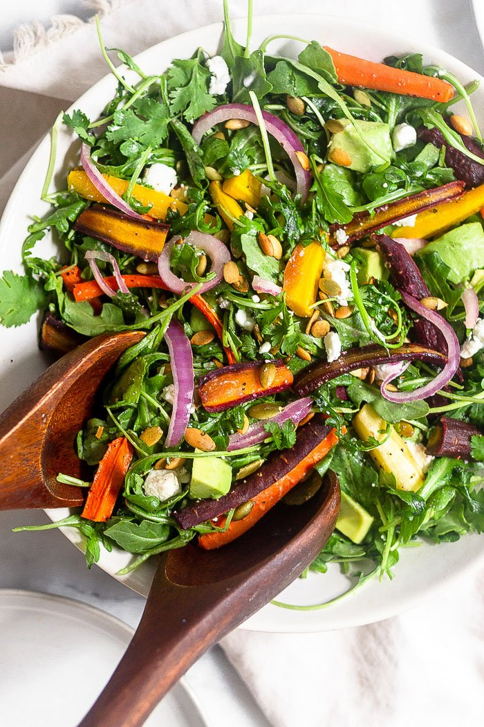 Large bowl filled with roasted carrot and arugula salad with two wooden salad tongs scooping some out