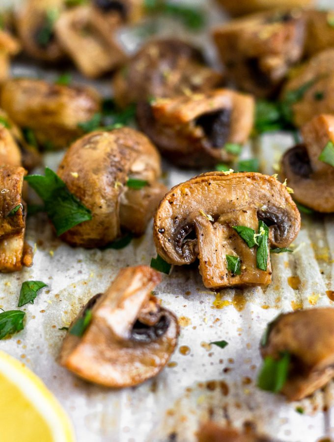 Close up of a balsamic roasted mushrooms on a baking sheet surrounded by more mushrooms. They are topped with fresh parsley.