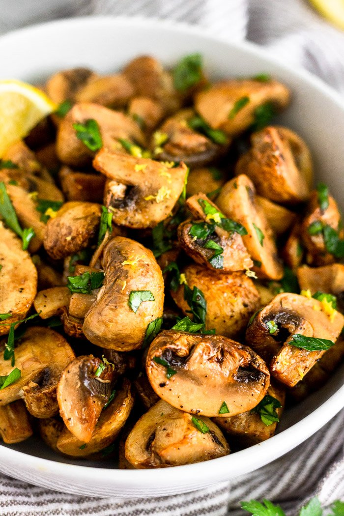Close up of a bowl filled with oven roasted mushrooms topped with fresh parsley and lemon zest.