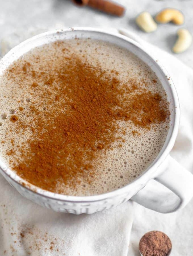 Large mug filled with collagen hot chocolate sprinkled with cinnamon. It is sitting on a towel and behind it is cinnamon sticks and cashews