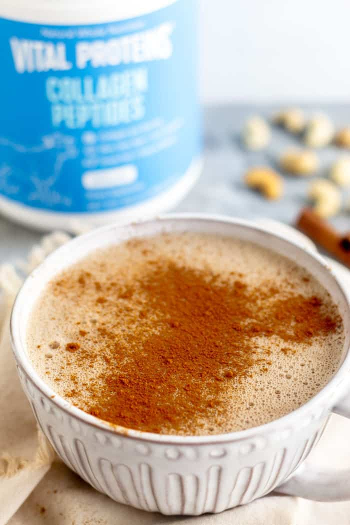 Large mug filled with paleo collagen hot chocolate. It is sprinkled with cinnamon. Behind it is a container of Vital Proteins Collagen, cinnamon sticks, and cashews