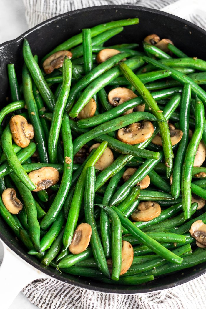 Cast iron skillet with sauteed green beans and mushrooms.