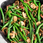 Cast iron skillet with green beans with mushrooms and onions.