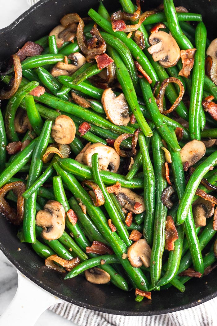 Close up of a large cast iron skillet with fresh green beans with bacon and onions and mushrooms.