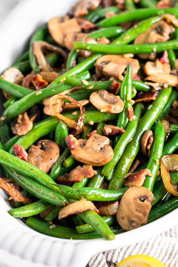 Sauteed green beans with bacon and mushrooms in a white casserole dish.