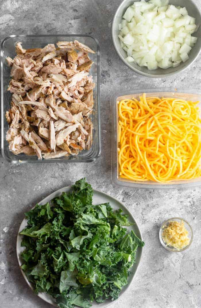 A grey surface with a big container of leftover turkey, a bowl of diced onion, a container of butternut squash noodles, a small bowl of ginger and garlic, and a plate of kale