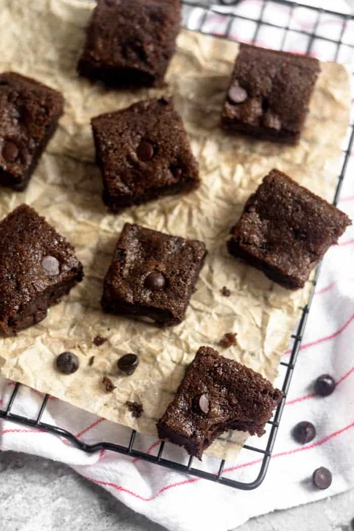 Multiple gluten free chocolate chip gingerbread blondies on a piece of parchment paper on a cookie drying rack. One of them as a bite taken out of it and they are surrounded by some crumbs and chocolate chips