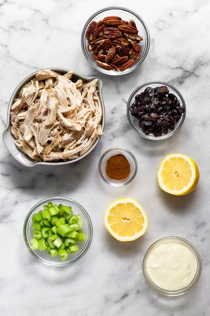 White counter top with a bowl of shredded chicken, bowl of pecans, bowl of dried cranberries, bowl of mayo, bowl of diced celery. bowl of cinnamon, and a lemon cut in half.