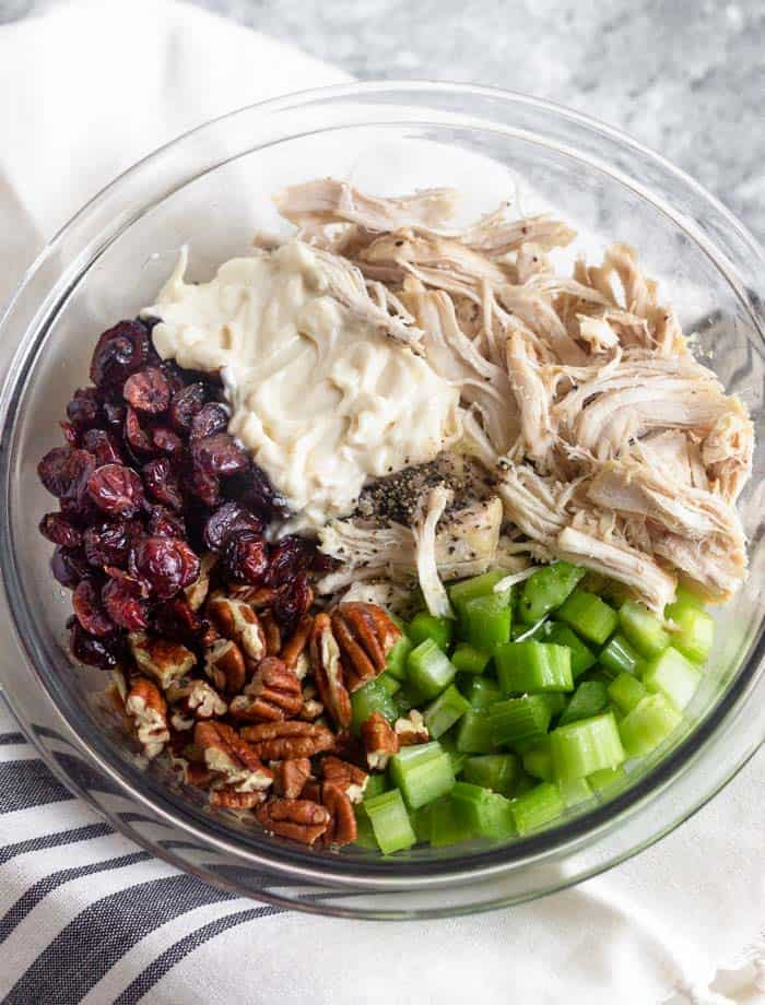 A bowl of shredded chicken, diced celery, pecans, dried cranberries, and mayo on a white and blue stripped towel.