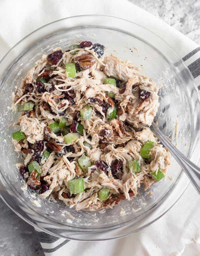 A large glass bowl filled with cranberry pecan chicken salad that was all mixed up. A spoon is coming out of it.