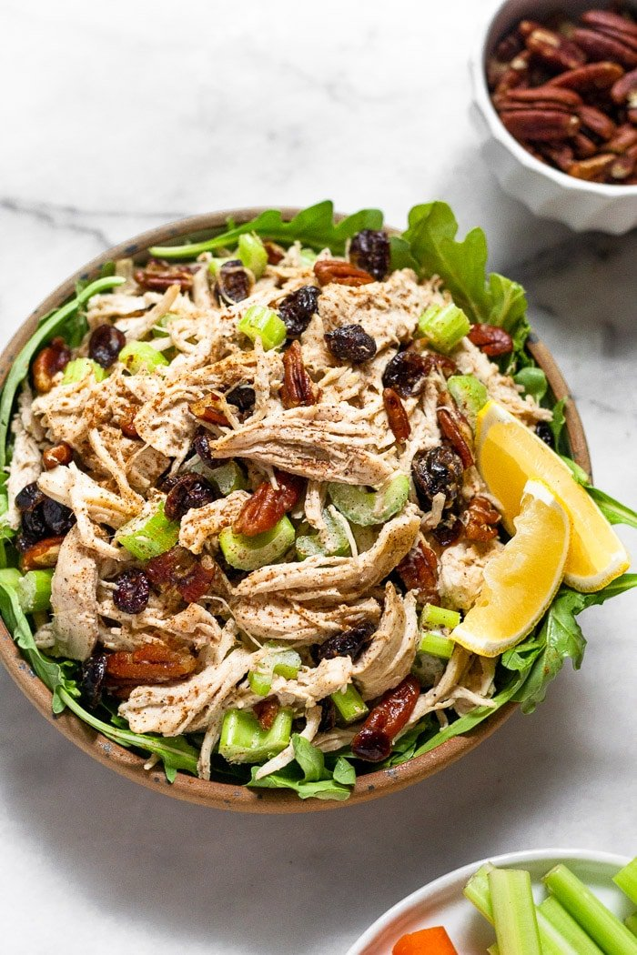 Bowl of pecan chicken salad with cranberries. Next to is a plate with celery and lemon wedges and a bowl of pecans.