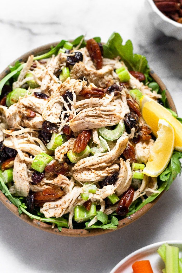 Close up of chicken salad with cranberries and pecans in a small bowl with greens and lemon wedges. There is a also a bowl of pecans behind it and a plate of carrots and celery in front of it.