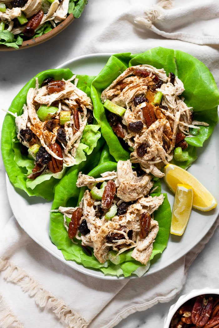 Three lettuce cups on a plate filled with chicken salad with cranberries and pecans and two lemon slices. The plate is sitting on a tan linen and next to it a bowl of more chicken salad and a small bowl of pecans.