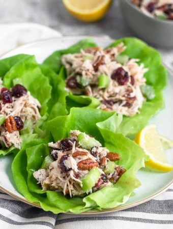 Three lettuce cups filled with cranberry pecan chicken salad on a white plate. Behind it is a bowl of more chicken salad and half a lemon.