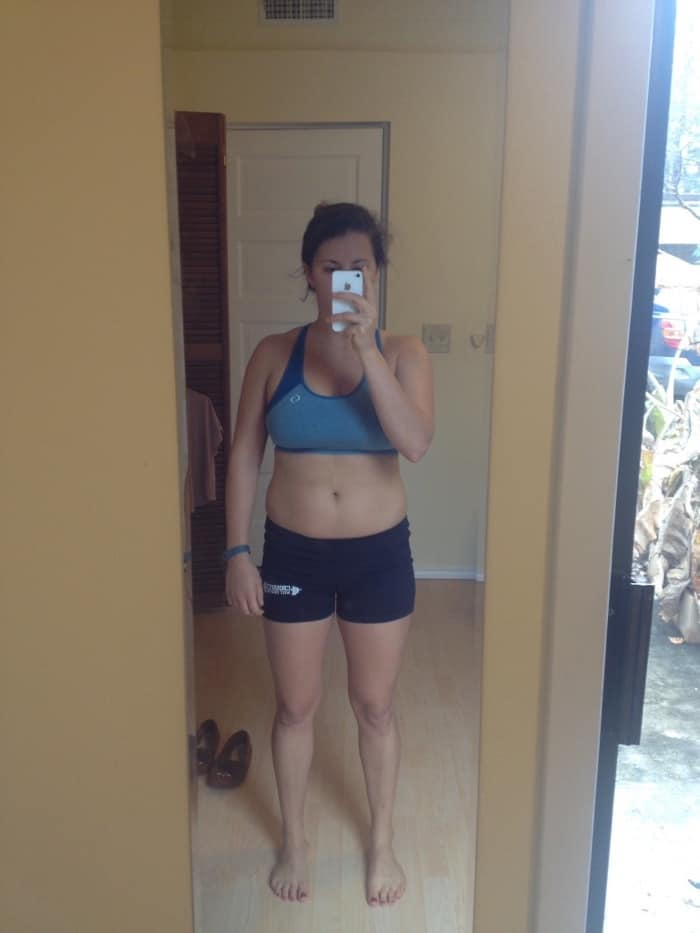 Girl in spandex shorts and a sports bra taking a selfie in front of a mirror.