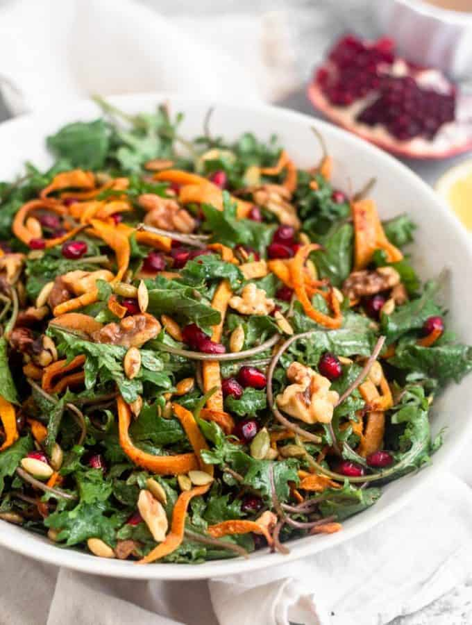 Large white bowl filled with a paleo kale salad with butternut squash and pomegranates. It also has walnuts and pumpkin seeds in it. Behind the bowl is a quarter of a pomegranate, half a lemon, and a small bowl of dressing further behind them.