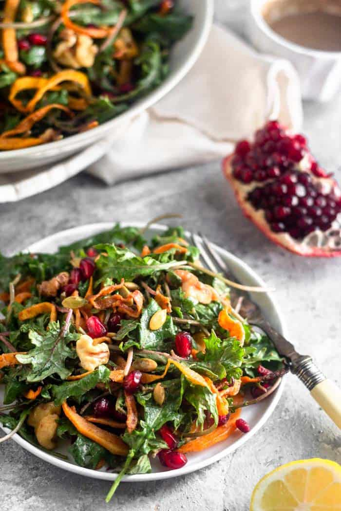 Small white plate filled with kale salad with butternut squash with a fork hanging off of it. Behind it is a quarter of a pomegranate, a small bowl of dressing, and a large bowl of more salad.